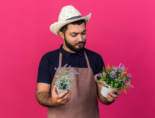 Geen idee, jonge blanke mannelijke tuinman met een tuinhoed die vasthoudt en kijkt naar bloempotten geïsoleerd op een roze muur met kopieerruimte