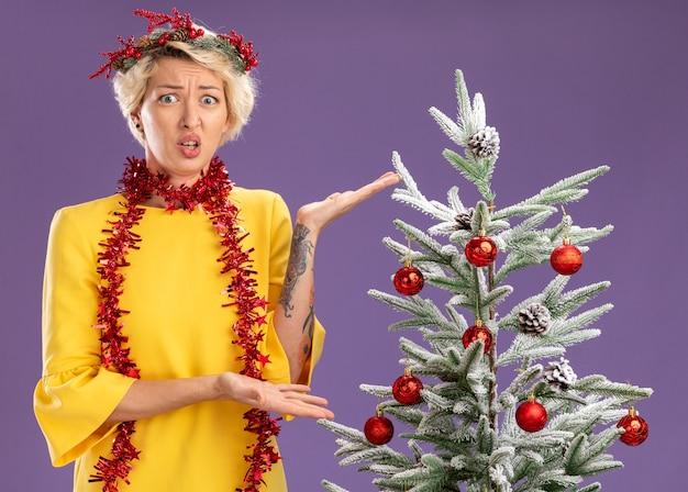 Geen idee, jonge blonde vrouw die de hoofdkrans van kerstmis en een klatergoudslinger om de nek draagt, die in de buurt van een versierde kerstboom staat en ernaar wijst met handen die geïsoleerd op een paarse muur kijken