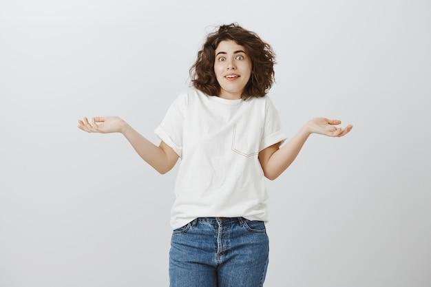 Geen idee, mooi meisje dat haar schouders ophaalt met zijwaarts gespreide handen, weet niets, heeft geen idee