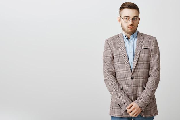 Geen idee, onhandige mannelijke werknemer die wegkijkt en er schuldig uitziet, iets verbergt