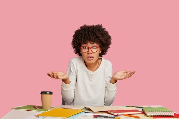 Geen idee van een donkere student met een aarzelende uitdrukking, haalt zijn schouders op, maakt huiswerk, poseert in de coworking space,