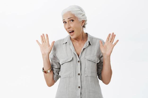 Geen idee, vrolijke oude dame die onaangeroerd haar hand opstak en in de war was