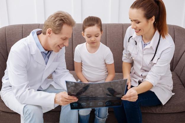 Geen ingewikkelde dingen. bekwame geduldige uitstekende chirurgen die eenvoudige woorden gebruiken om het meisje haar diagnose uit te leggen terwijl ze met hen naar haar hersenscans kijkt
