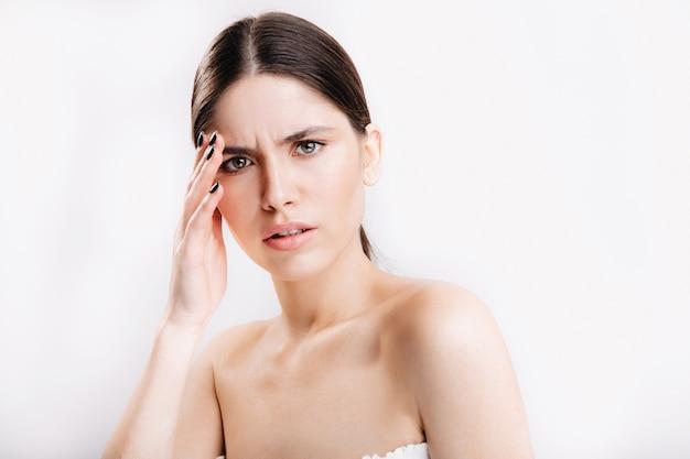 Geen make-up vrouwelijk portret op geïsoleerde muur. vrouw met grijze ogen heeft hoofdpijn.