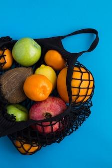 Geen plastic zakconcept. zwarte boodschappentas van mesh met verschillende soorten fruit op het blauw