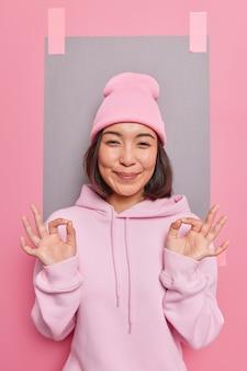 Geen probleem. tevreden oprechte aziatische vrouw verzekert dat alles onder controle is, keurt iets goeds goed assertief zijn in haar keuze garandeert kwaliteit draagt hoed en casual sweatshirt poseert binnen