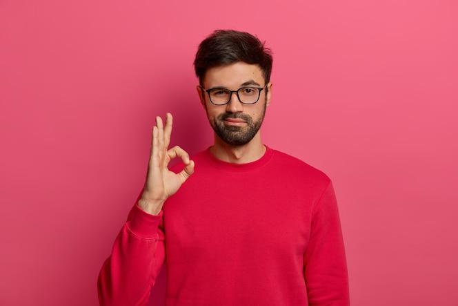 Geen probleemconcept. bebaarde man maakt ok gebaar, heeft alles onder controle, allemaal fijn gebaar, draagt bril en trui, poseert tegen roze muur, zegt dat ik dit heb, garandeert iets