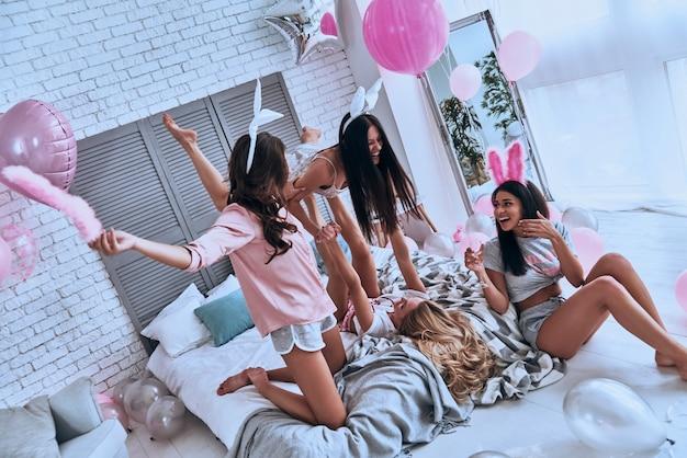 Geen regels voor hen. speelse jonge vrouwen in konijnenoren die plezier hebben en glimlachen terwijl ze genieten van een thuisfeest