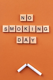 Geen rookvrije dag concept. gebroken sigaret en houten blokken met letters geïsoleerd op een oranje achtergrond.