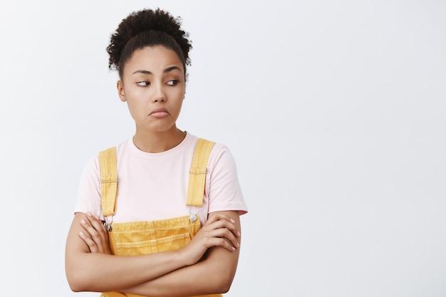 Geen slechte, mooie schoenen, wil ze ook. zelfverzekerde coole afro-amerikaanse vrouw in gele overall, lippen tuitend en naar rechts starend, hand in hand op de borst gekruist, iets leuk vinden, het bekijken