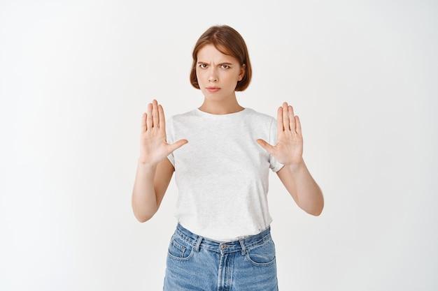 Geen stop daar. ernstige vrouw die haar hand opsteekt voor blokkade, teleurgesteld fronst, een slecht aanbod afwijst, een negatieve mening uitdrukt en weigert, staande op een witte muur