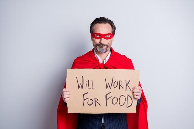 Geen superman meer. foto van gestresste ontevreden volwassen zakenman superheld kostuum houd karton plakkaat nodig baan werkkleding pak rood gezichtsmasker mantel geïsoleerde grijze achtergrond