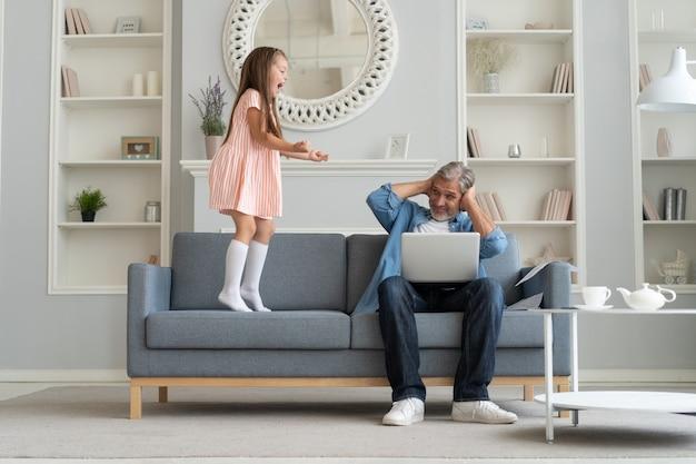 Geen tijd voor kind. grijsharige vader bezig met laptop, thuis online aan het werk, verdrietig verveelde beledigde dochter die dichtbij springt.