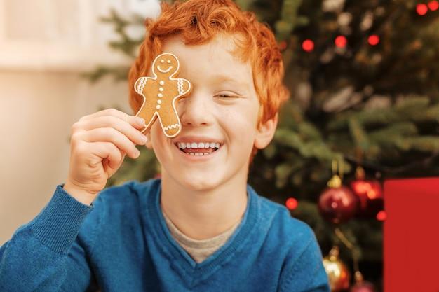 Geen tijd voor zorgen. portret van een stralende roodharige jongen die een grapje maakt en vrolijk lacht terwijl hij plezier maakt en speelt met een handgemaakte peperkoekman.