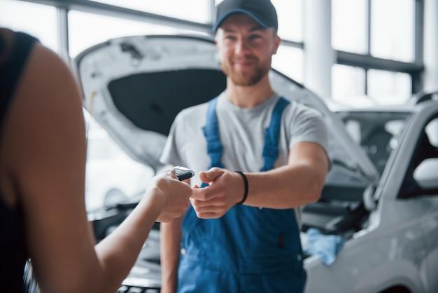 Geen zorgen, alles komt goed. vrouw in de autosalon met werknemer in blauw uniform die haar gerepareerde auto terugneemt