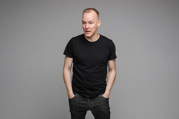 Geënsceneerde foto van een blanke man in zwarte kleding die zijn handen in de zakken houdt en er verward uitziet