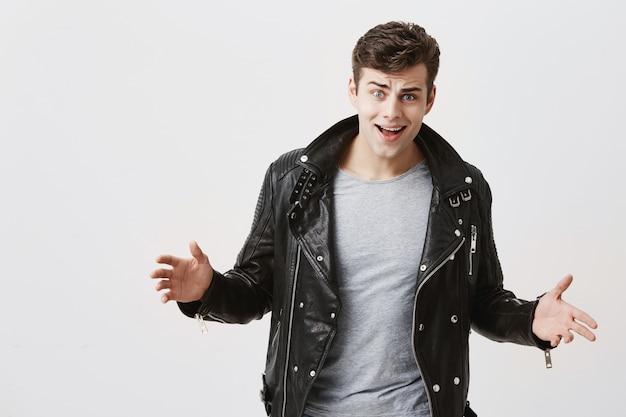 Geërgerd aantrekkelijke mannelijke gebaren met irritatie, handpalmen openhoudend, gekleed in zwartleren jasje en spijkerbroek, fronst het gezicht vanwege miscommunicatie. negatieve menselijke emoties en reacties.