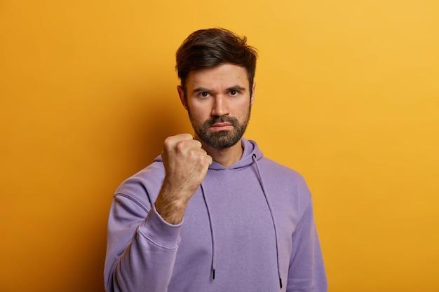 Geërgerd agressieve blanke man toont vuist, verliest zijn geduld, kijkt naar persoon met haat, belooft wraak te nemen, gekleed in een paarse hoodie, geïsoleerd op een gele muur. negatieve emoties concept
