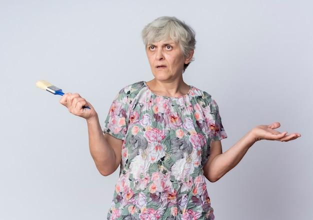 Geërgerd bejaarde vrouw houdt penseel kijken kant geïsoleerd op een witte muur