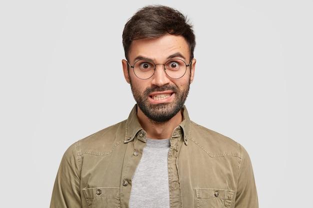 Geërgerd blanke man trekt wenkbrauwen op, klemt zijn tanden op elkaar en kijkt boos, draagt een ronde bril en overhemd, drukt negativiteit uit, staat tegen een witte muur. mensen en emoties concept