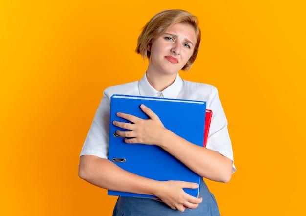 Geërgerd blond russisch meisje houdt bestandsmappen geïsoleerd op een oranje achtergrond met kopie ruimte