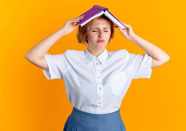 Geërgerd blond russisch meisje houdt boek boven het hoofd geïsoleerd op een oranje achtergrond met kopie ruimte