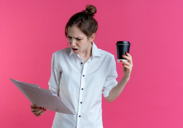 Geërgerd blond russisch meisje kijkt naar vellen papier met koffiekopje geïsoleerd op roze ruimte met kopie ruimte