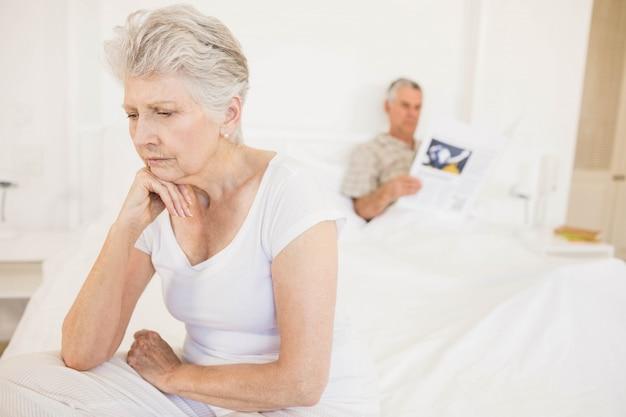 Geërgerd echtpaar negeren elkaar in de slaapkamer