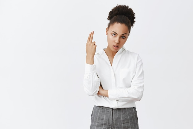 Geërgerd en gehinderd afro-amerikaanse zakenvrouw rollen ogen en hijgend, waardoor handpistoolgebaar verveeld