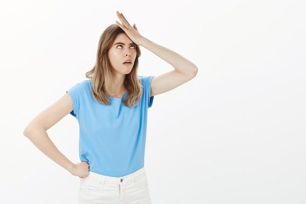 Geërgerd en gehinderd blonde vrouw oogrol en klap voorhoofd verontrust, kijkend geïrriteerd
