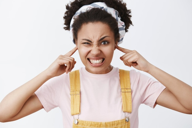 Geërgerd en ontevreden schattige afro-amerikaanse vrouwelijke stijlvolle student in gele overall en hoofdband, oren sluiten met vingers, fronsen, tanden op elkaar klemmen