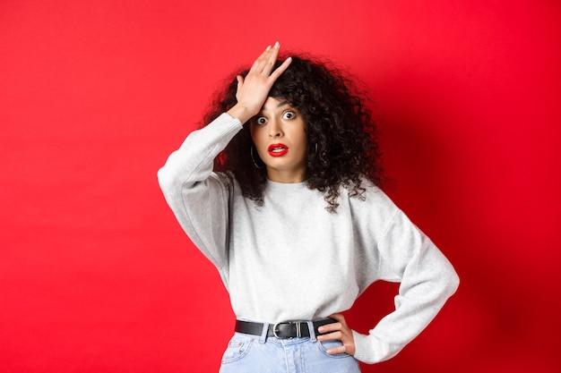 Geërgerd en vermoeide jonge vrouw klap voorhoofd, gezicht palmen en staren camera geschokt, staande gehinderd tegen rode achtergrond.