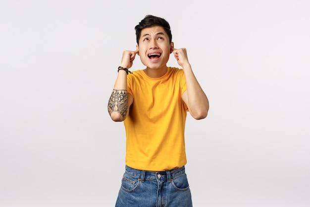 Geërgerd, gehinderd en ontevreden jonge aziatische mannelijke student kan niet studeren, buren boven geven luid feest, draaien vervelende muziek, man kijkt omhoog, sluit oren met vingers en schreeuwt gestoord