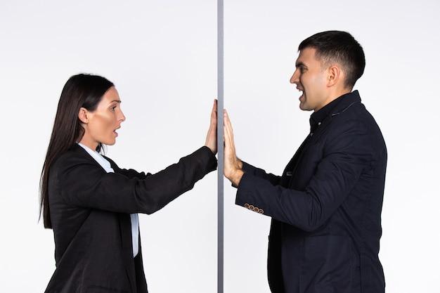 Geërgerd geslacht bedrijfsondernemers dichtbij de muur op een witte geïsoleerde achtergrond