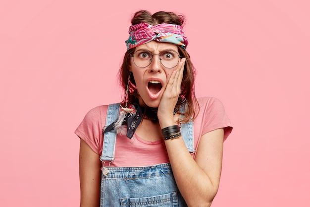 Geërgerd hippie-vrouwtje met negatieve gezichtsuitdrukking, houdt hand op wang, opent mond wijd, ontevreden over het laatste nieuws, poseert tegen roze muur. geïrriteerde hippievrouw binnen.