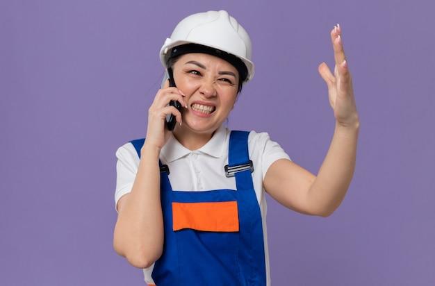 Geërgerd jong aziatisch bouwersmeisje met witte veiligheidshelm die tegen iemand op telefoon schreeuwt die hand open houdt