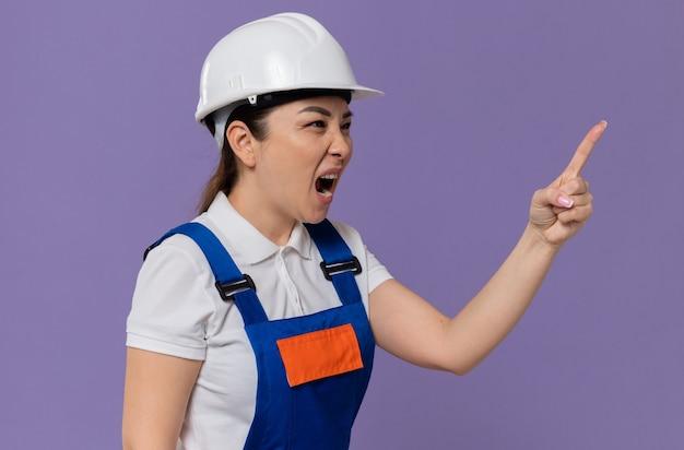 Geërgerd jong aziatisch bouwmeisje met een witte veiligheidshelm die naar de zijkant kijkt en naar iemand schreeuwt