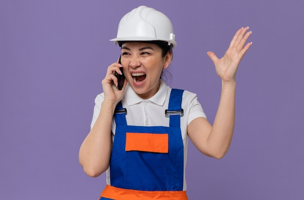 Geërgerd jong aziatisch bouwmeisje met witte veiligheidshelm die tegen iemand aan de telefoon schreeuwt die naar de zijkant kijkt