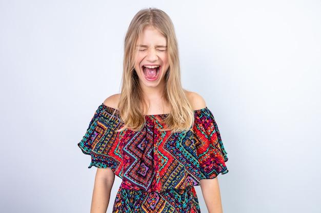 Geërgerd jong blond slavisch meisje dat schreeuwt met gesloten ogen