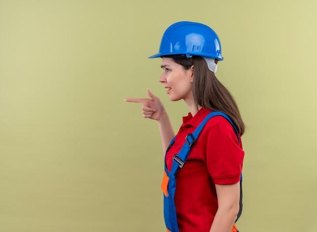Geërgerd jong bouwersmeisje met blauwe veiligheidshelm staat zijwaarts en wijst naar de kant op geïsoleerde groene achtergrond met exemplaarruimte