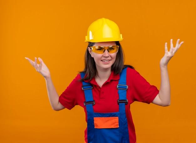 Geërgerd jong bouwersmeisje met veiligheidsbril hief beide handen op op geïsoleerde oranje achtergrond