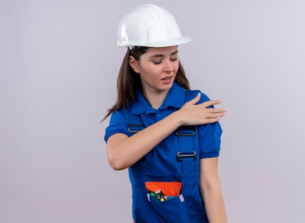 Geërgerd jong bouwersmeisje met witte veiligheidshelm en blauw uniform beweert haar schouder op geïsoleerde witte achtergrond met exemplaarruimte schoon te maken