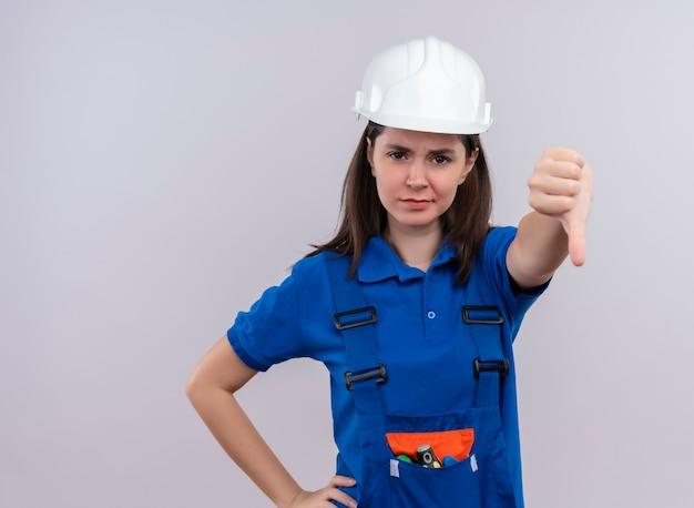 Geërgerd jong bouwersmeisje met witte veiligheidshelm en blauw uniform duimen neer op geïsoleerde witte achtergrond met exemplaarruimte