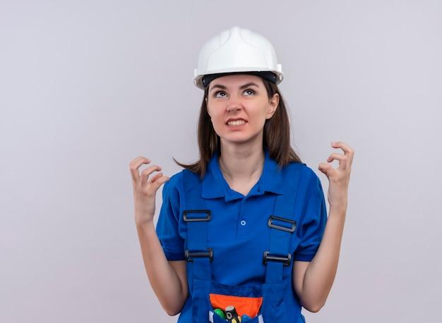 Geërgerd jong bouwersmeisje met witte veiligheidshelm en blauw uniform houdt handen omhoog en kijkt omhoog op geïsoleerde witte achtergrond met exemplaarruimte