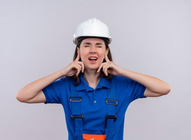 Geërgerd jong bouwersmeisje met witte veiligheidshelm en blauw uniform houdt oren met vingers op geïsoleerde witte achtergrond met exemplaarruimte