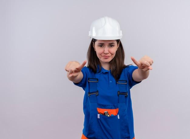 Geërgerd jong bouwersmeisje met witte veiligheidshelm en blauw uniform wijst naar voren met beide handen op geïsoleerde witte achtergrond met exemplaarruimte
