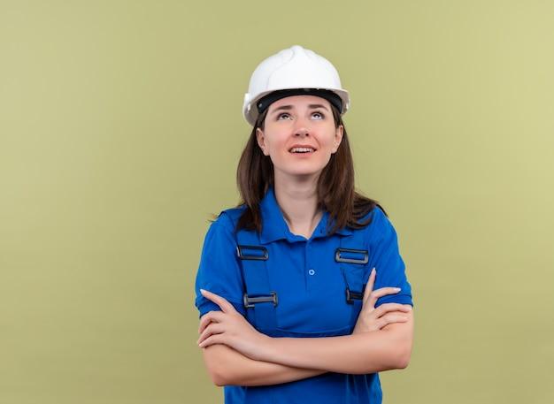 Geërgerd jong bouwersmeisje met witte veiligheidshelm en blauwe uniforme gekruiste armen en kijkt omhoog op geïsoleerde groene achtergrond met exemplaarruimte