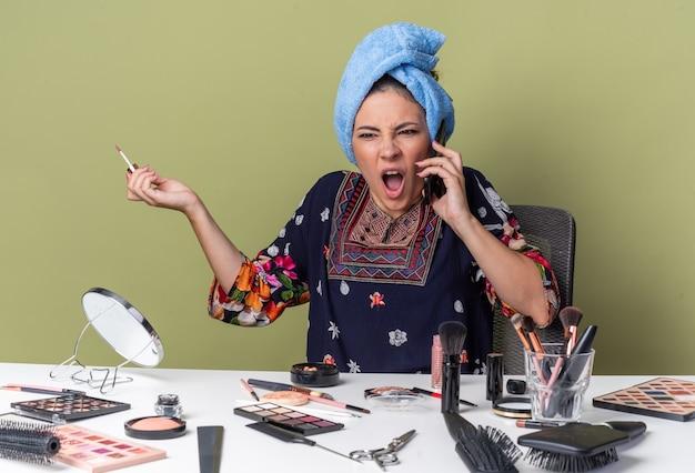 Geërgerd jong brunette meisje met gewikkeld haar in een handdoek zittend aan tafel met make-up tools schreeuwen tegen iemand aan de telefoon en houden lipgloss geïsoleerd op olijf groene muur met kopie ruimte