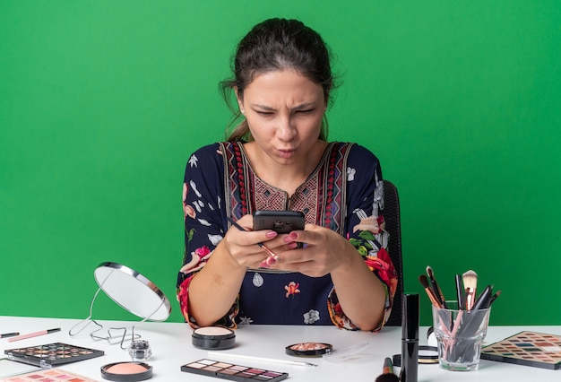 Geërgerd jong brunette meisje zittend aan tafel met make-up tools houden en kijken naar telefoon geïsoleerd op groene muur met kopieerruimte