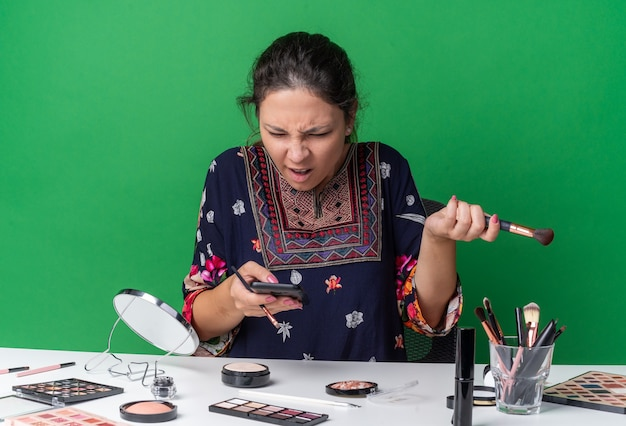 Geërgerd jong brunette meisje zittend aan tafel met make-up tools met make-up kwasten en kijken naar telefoon geïsoleerd op groene muur met kopie ruimte